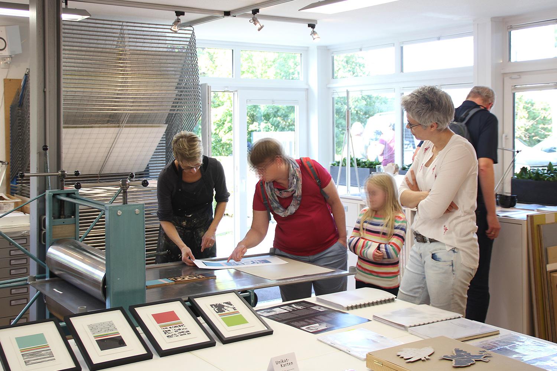 Offenes Atelier 2019   Druckdemonstration   interessierte Besucher die mir beim Drucken über die Schulter schauen