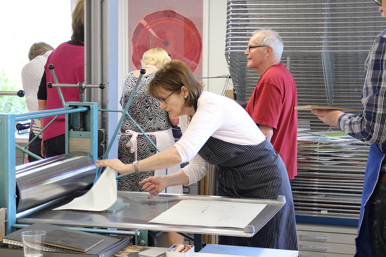 Kursteilnehmerin beim Abnehmen des frisch bedruckten Druckbogens