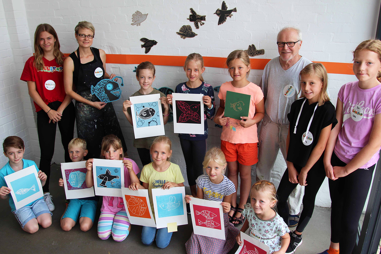 Momentaufnahme | Gruppenfoto einiger beteiligter Kinder zusammen mit mir als Dozentin und einem Teil der Helfer vor der sich in Arbeit befindlichen Wandinstallation | Pressefoto: Elvira Meisel-Kemper