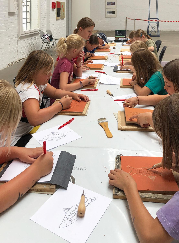 Kinder bei der Bearbeitung ihrer Druckplatten